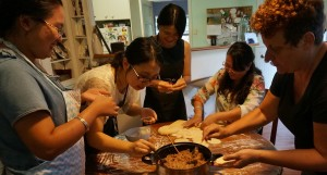 Five people standing around a kitchen table making Chinese dumplings