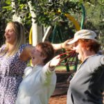 Three women tretching and laughing in a park