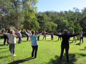 a circle of 20 people arms outstretched laughing in a park
