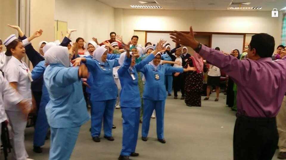Hosiptal staff are in a training session, arms outstretched and laughing, with Dr Arul Kumaran.