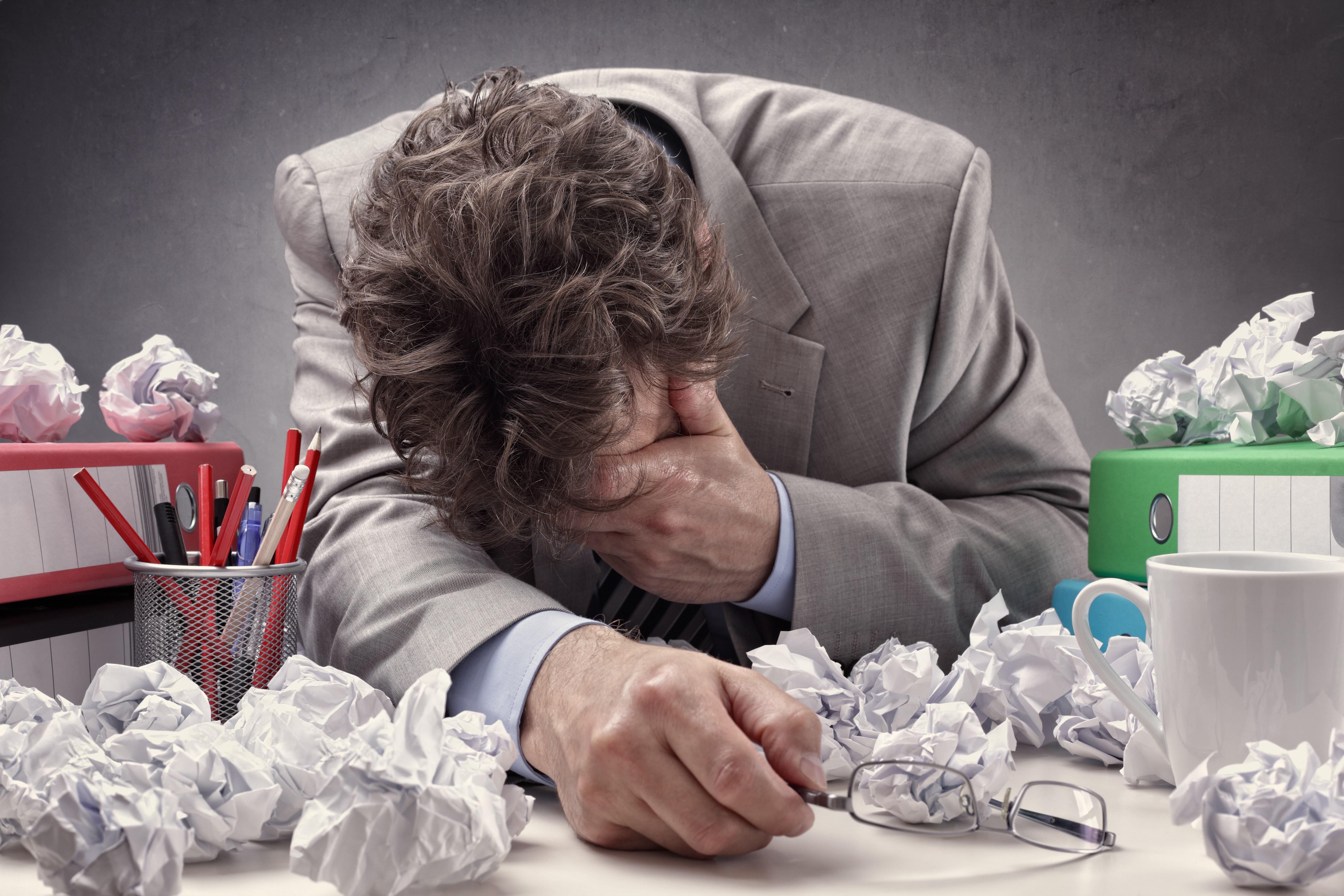 Overworked, depressed and exhausted office workers at his desk surrounded by a pile of work