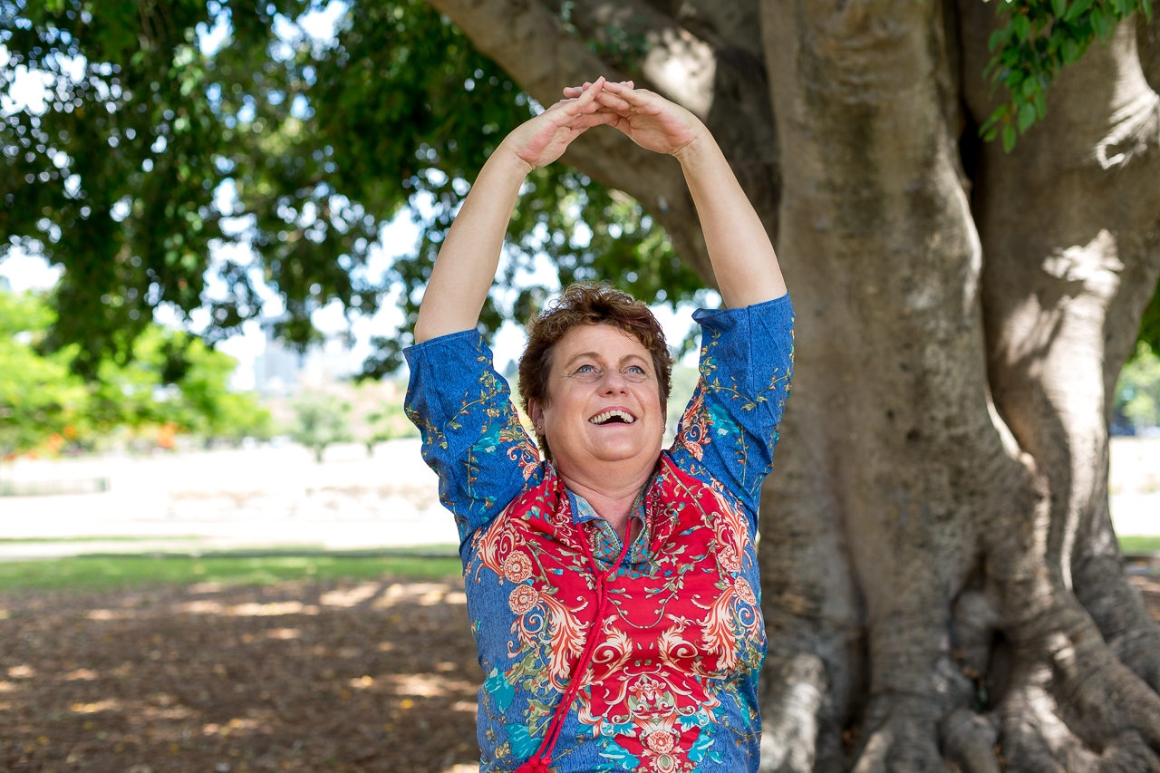 A woman stretching her arms above her head in a laughter yoga pose