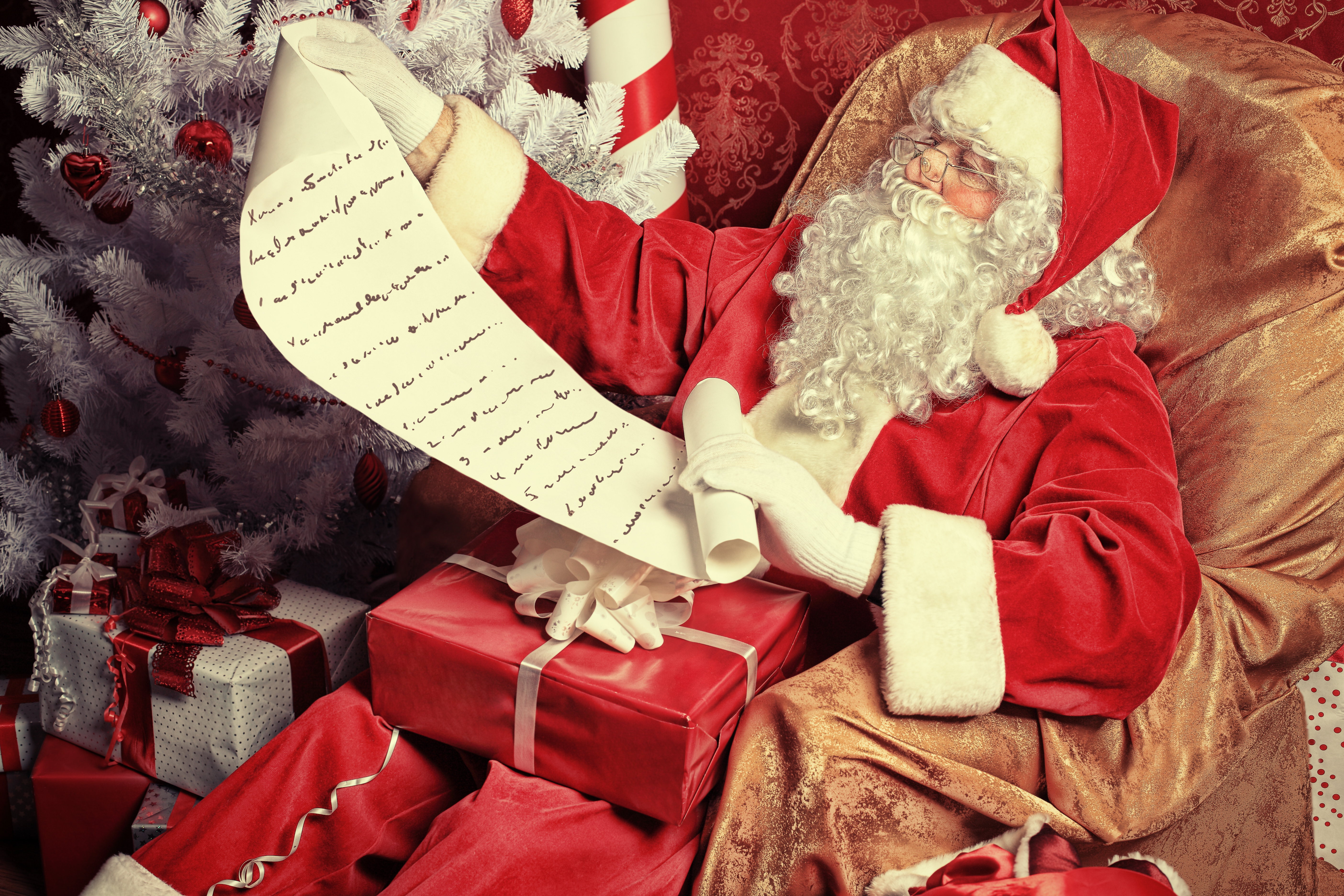 Santa Claus looks at a very long wish list. He is surrounded by presents and a Christmas tree.