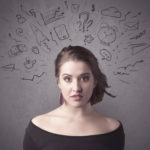 A dark brown haired young woman with thoughts in her head illustrated by question mark, rocket, money, coffee, clock, email, social life icons drawn on the background wall concept.