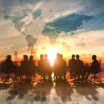 Group of business men and women seated around a board table in silhouette against a backdrop map of the world.
