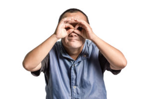 A man with Downs sydrome holds his hands to his eyes as though looking through glasses.